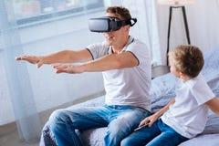 muchacho Pre-adolescente que mira su juego del padre con las auriculares de VR Fotos de archivo libres de regalías