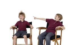 muchacho Pre-adolescente que señala en el pelo del amigo mientras que se sienta en la silla del director sobre el fondo blanco Foto de archivo libre de regalías