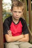 Muchacho pre-adolescente triste que se sienta afuera Fotos de archivo