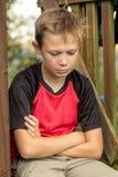 Muchacho pre-adolescente triste que se sienta afuera Fotografía de archivo