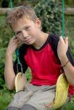 Muchacho pre-adolescente triste que se sienta en un oscilación Imagenes de archivo