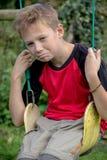 Muchacho pre-adolescente triste que se sienta en un oscilación Fotos de archivo