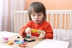 Muchacho precioso con el playdough Foto de archivo libre de regalías