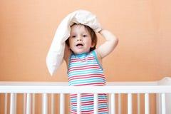 Muchacho precioso con la almohada en la cabeza en la cama blanca Foto de archivo libre de regalías
