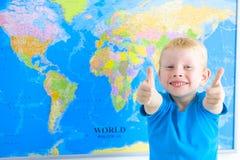 Muchacho preescolar con el mapa del mundo, pulgares para arriba Imagen de archivo libre de regalías