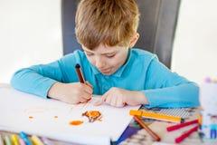 Muchacho preescolar del niño en casa que hace la preparación, pintando una historia con las plumas coloridas Imagen de archivo libre de regalías
