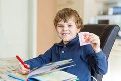 Muchacho preescolar del niño en casa que hace letras de la escritura de la preparación con las plumas coloridas Imágenes de archivo libres de regalías