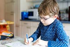 Muchacho preescolar del niño en casa que hace letras de la escritura de la preparación con las plumas coloridas Fotos de archivo