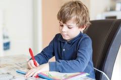 Muchacho preescolar del niño en casa que hace letras de la escritura de la preparación con las plumas coloridas Fotos de archivo libres de regalías