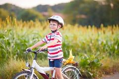 Muchacho preescolar del niño en el casco que se divierte con el montar a caballo de la bicicleta Imagen de archivo