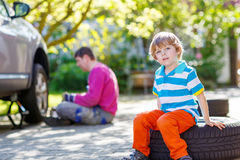 Muchacho preescolar del niño que se sienta en la rueda de coche durante su repairi del padre Fotografía de archivo