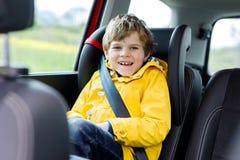 Muchacho preescolar lindo adorable del niño que se sienta en coche en capa de lluvia amarilla Imagen de archivo libre de regalías