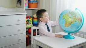 Muchacho preescolar que explora el mundo en el globo del mundo metrajes