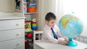 Muchacho preescolar que explora el mundo en el globo del mundo almacen de video