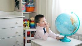 Muchacho preescolar que explora el mundo en el globo HD del mundo metrajes