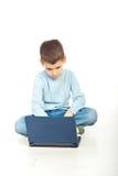 Muchacho preescolar que usa el cuaderno Imagen de archivo