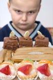 Muchacho prohibido comer las tortas Fotos de archivo