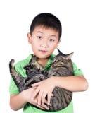Muchacho que abraza con su gato de tigre lindo aislado en el fondo blanco Foto de archivo libre de regalías
