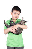 Muchacho que abraza con su gato de tigre lindo aislado en el fondo blanco Imagen de archivo