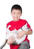 Muchacho que abraza con su gato lindo aislado en el fondo blanco Imagenes de archivo