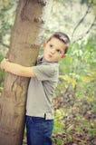 Muchacho que abraza el árbol Imagen de archivo