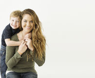 Muchacho que abraza a su mamá de ella detrás Imágenes de archivo libres de regalías