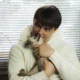 Muchacho que abraza un gato gris hermoso imagenes de archivo