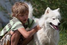 Muchacho que abraza un perro mullido Imagenes de archivo