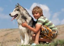 Muchacho que abraza un perro mullido Foto de archivo