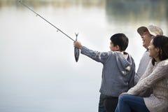 Muchacho que admira la captura de pesca con la familia en el lago Foto de archivo libre de regalías
