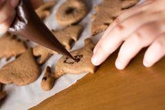 Muchacho que adorna las galletas del pan de jengibre con el chocolate Fotografía de archivo