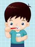 Muchacho que aplica sus dientes con brocha Imágenes de archivo libres de regalías