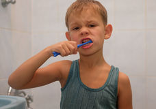 Muchacho que aplica sus dientes con brocha Foto de archivo libre de regalías