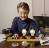 Muchacho que aprende con el experimento de la electricidad Foto de archivo