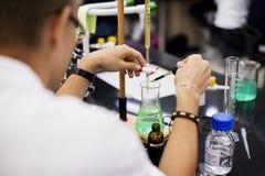 Muchacho que aprende la sala de clase de la ciencia química Imagen de archivo libre de regalías