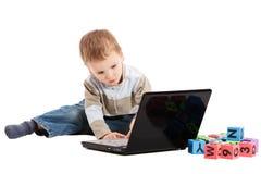 Muchacho que aprende leer con los bloques y el ordenador de los cabritos Imágenes de archivo libres de regalías