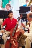 Muchacho que aprende tocar el violoncelo en orquesta de la High School secundaria Foto de archivo