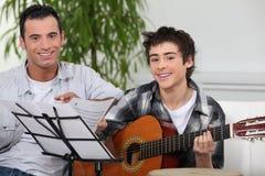 Muchacho que aprende tocar la guitarra Imagen de archivo