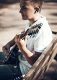Muchacho que aprende tocar la guitarra Imagenes de archivo