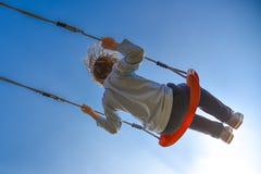 Muchacho que balancea el cielo muy alto, azul en fondo Foto de archivo