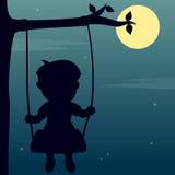 Muchacho que balancea en el claro de luna Fotografía de archivo libre de regalías
