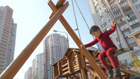 Muchacho que balancea en el oscilación de madera Patio de madera con el balanceo del niño Concepto feliz de la ni almacen de metraje de vídeo