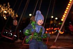 Muchacho que balancea en un oscilación en la noche Imagen de archivo libre de regalías