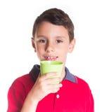 Muchacho que bebe de la taza plástica Foto de archivo