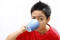 Muchacho que bebe de una taza Fotos de archivo
