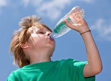 Muchacho que bebe el agua dulce al aire libre Fotos de archivo