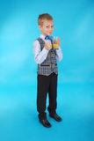 Muchacho que bebe el zumo de naranja y que muestra el pulgar para arriba Foto de archivo libre de regalías