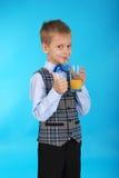 Muchacho que bebe el zumo de naranja y que muestra el pulgar para arriba Imagen de archivo