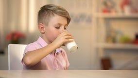 Muchacho que bebe la leche orgánica fresca del vidrio en la tabla, comida de la energía de la mañana, lechería almacen de metraje de vídeo