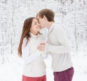 Muchacho que besa a la muchacha en bosque del invierno Foto de archivo libre de regalías